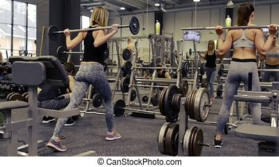 Young people in gym working out with various barbells