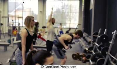 Young people in gym working out with various barbells -...