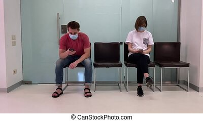 Young people in medical masks, sitting in a queue and ...