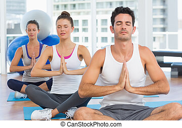 Young people in Namaste pose with eyes closed - Three sporty...