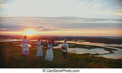 Young people in russian traditional clothes having fun on the field on a background of beautiful sunset - singing, dancing