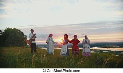 Young people in russian traditional clothes having fun on the field - singing, dancing
