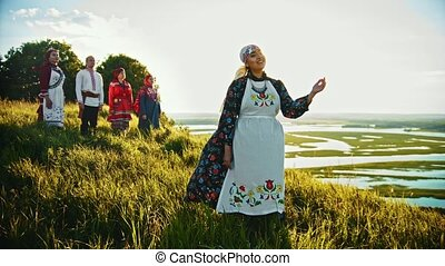 Young people in russian traditional clothes standing on the field and woman singing a song - enjoying the view on sunset