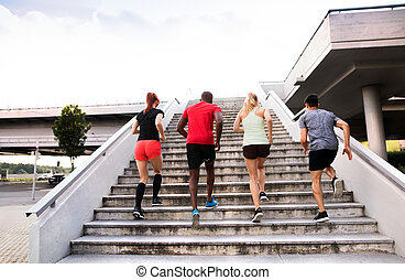 Young people in the city running up the stairs.