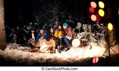 Young people in the winter forest sitting by the fire. A cute couple kiss. Happy group of friends enjoying their holidays