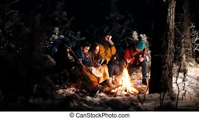 Young people in the winter forest sitting by the fire. Frying food on the fire
