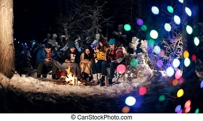 Young people in the winter forest sitting by the fire. People sitting in their phones