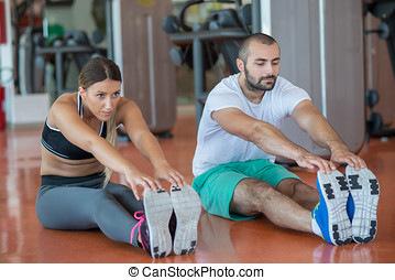 Young people involved in sports. Woman stretching with...