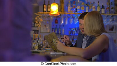 Young people looking at menu in the bar