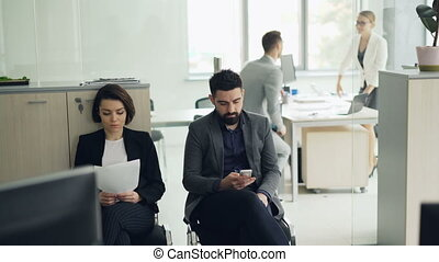 Young people man and woman are waiting for job interview in...