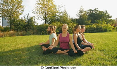 Young people meditating outdoors