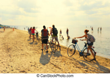Young people on bicycles on a sandy beach. Blurry