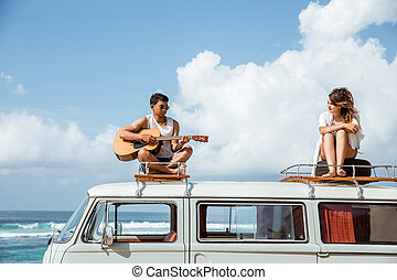 young people on roof of retro styled minivan enjoying time toget