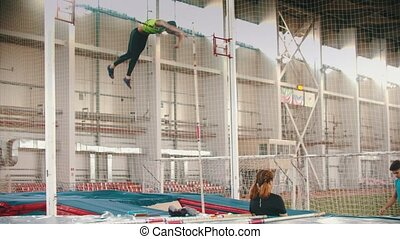 Young people on the pole vault training on the closed stadium. Mid shot