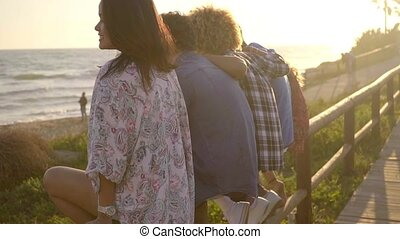 Young People On Wooden Fence. - Rear view of five young...