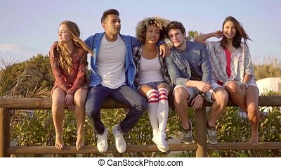 Young People On Wooden Fence. - Young people sitting on...