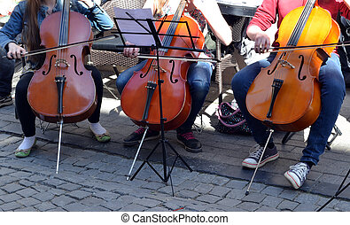 Young people playing cello violoncello bass-viol in street music day in Old Town street. Free event.