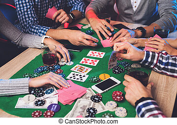 Young people play poker at the table. On the table they have...