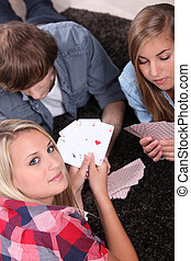 Young people playing cards with a girl showing the winning hand