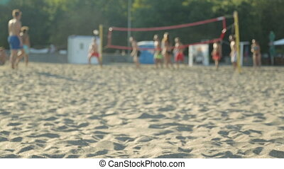 Young people playing volleyball on beach