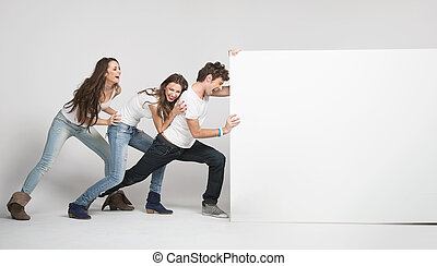 Young people pushing white board - Young happy people...