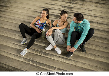 Young people  resting on stairs after training
