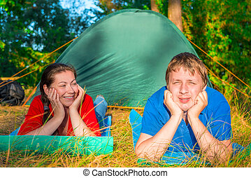young people resting on the grass near tent