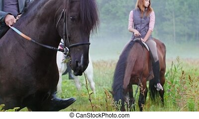 Young people riding horses in nature, brown horse chews grass in the foreground