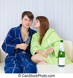 Young people sit at home on sofa in dressing gowns with fizz