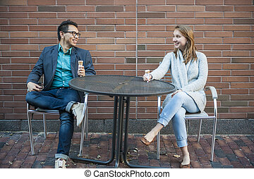 Young people sitting on patio - Two smiling young people ...