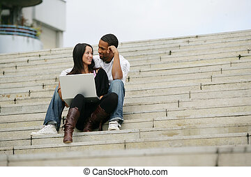 Young people sitting on steps of stairs with laptop