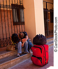 Young people sleeping on the sidewalk  nex to a trolley