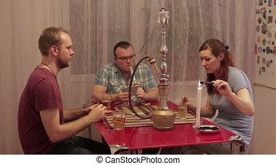 Young people smoking shisha and playing cards