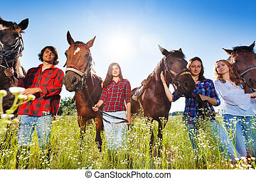 Young people standing in a row with their horses