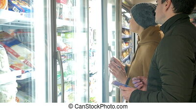 Young people taking product in fridge section