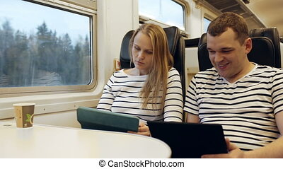 Young people talking in the train looking on the tablet PC