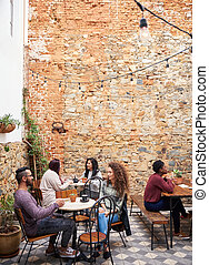 Young people talking over coffee in a cafe courtyard
