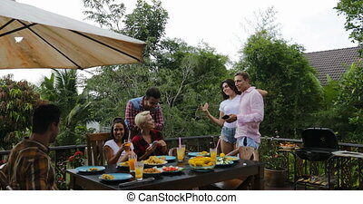 Young People Talking Sitting At Table Cooking Barbecue...