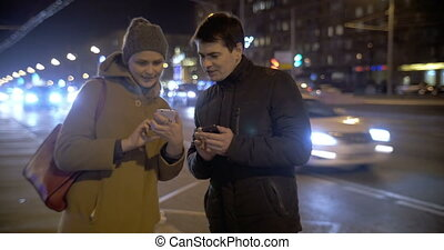 Young people using cells and talking in the street
