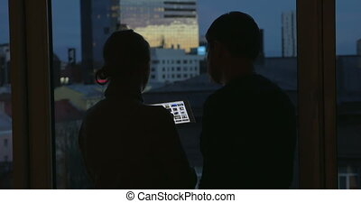 Young people using pad by the window at night