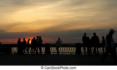 Young people walk in park on embankment in evening, time lapse