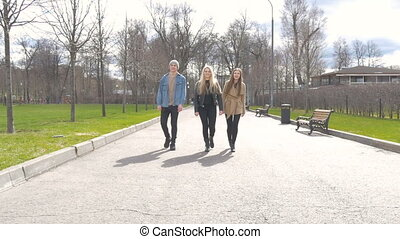 Young people walk in the park, tell the news, communicate, laugh. Good mood.