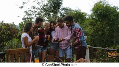 Young People Watch Photos Using Cell Smart Phone Cooking...