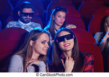 Young people watching 3D film at the movie theatre