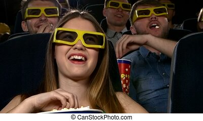 young people watching 3d movie at movie theater: comedy. Close up