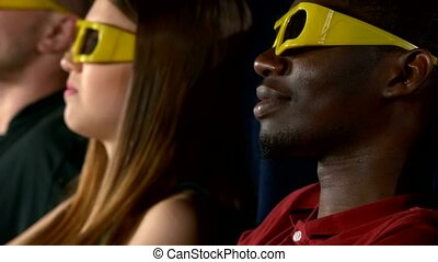 young people watching movie at movie theater, close up