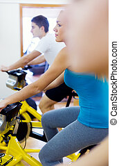 Young people with fitness bicycle in the gym.