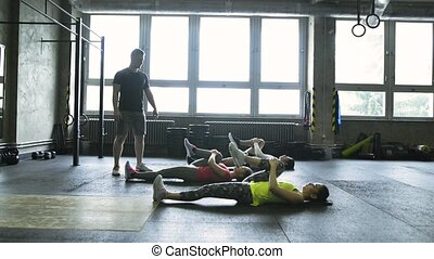 Young people with trainer in crossfit gym stretching their legs.