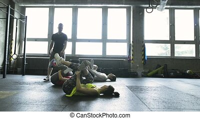 Young people with trainer in crossfit gym stretching their...