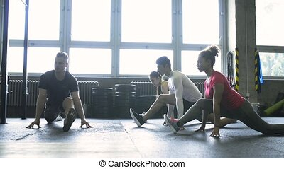 Young people with trainer in crossfit gym stretching legs. -...
